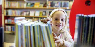 Leseglad: Tori Torbjørnsen (7) er dotter til biblioteksjef Silje Vågen Torbjørnsen. Ho har arva interessa for bøker, og har lese såpass mykje at ho har gjort seg fortent til tre premiar på biblioteket denne sommaren. Foto: Marius Knutsen/Sunnhordland